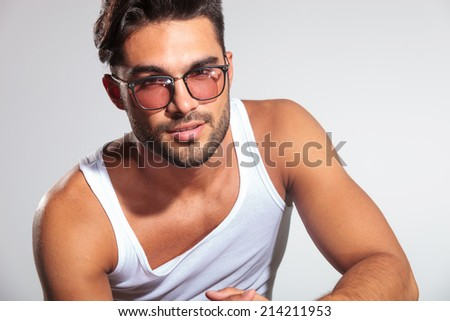 head and shoulders picture of a cute fit man with glasses in studio