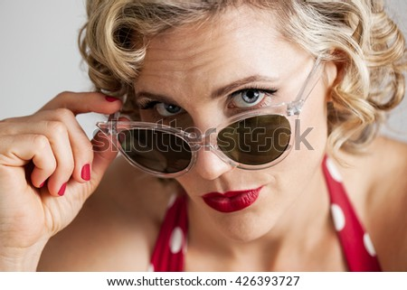 Head and shoulders portrait of a beautiful mid 30s woman dressed with retro vintage hair and makeup peeking behind sunglasses