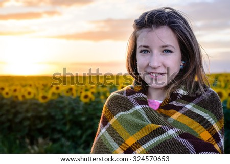 Head and Shoulders Portrait of Brunette Girl Wrapped in Plaid Blanket and Smiling at Camera in front of Sunflower Field at Sunset with Warm Golden Sun and Copy Space