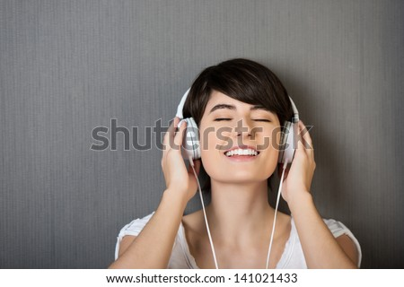 Head and shoulders studio portrait of a young woman listening to music on a set of headphones standing with her eyes closed in bliss