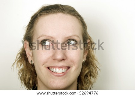 Head of young blond woman with eyes turned into left upper corner. Lot of space around.