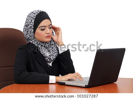 Headache and Stress at work. Young professional muslim woman stressed and tired with headache sitting at office desk