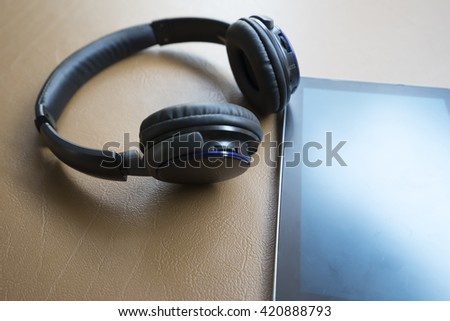 headphone and digital tablet on brown leather cushion