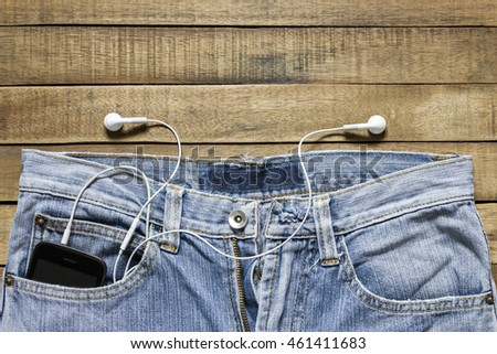 Headphones hanging off a jeans pocket on wood background.
