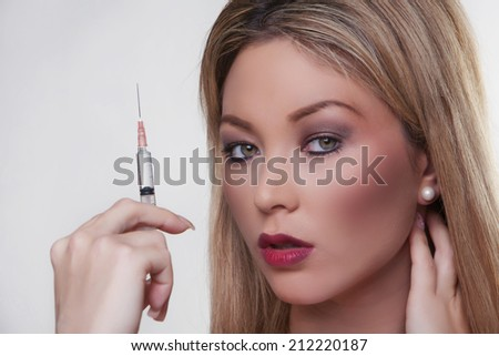 headshot of beautiful female model holding a syringe