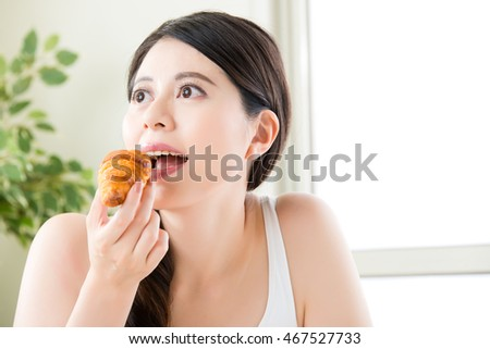 health asian smile woman eating croissant, healthy food concept indoor background