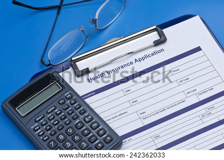 Health insurance application with glasses, and calculator.