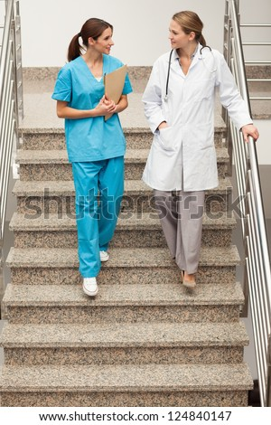 Health specialists going down the stairs in a hospital