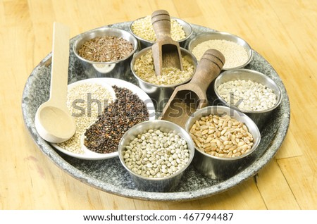 Healthy ancient grains and gluten free seeds in stainless steel containers with wooden scoops