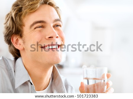 Healthy and happy young man holding glass of water while relaxin