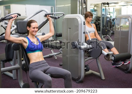 Healthy brunette using weights machine for arms at the gym