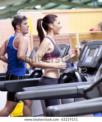 Healthy couple running on a treadmill in a sport centre