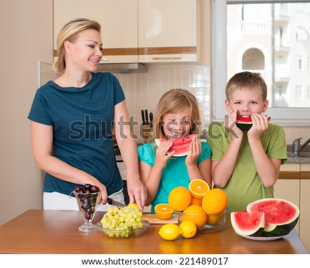 Healthy eating - mother and children eating watermelon, lots of fresh fruit on the table in front. family in the kitchen with different kinds of fruits for breakfast food.  Funny playful kids