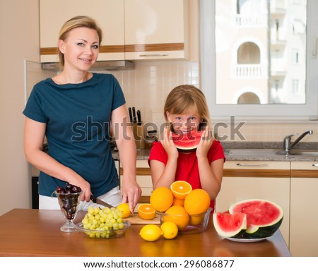 Healthy eating.? Mother and daughter eating watermelon, lots of fresh fruit on the table in front. Family in the kitchen with different kinds of fruits for breakfast food.