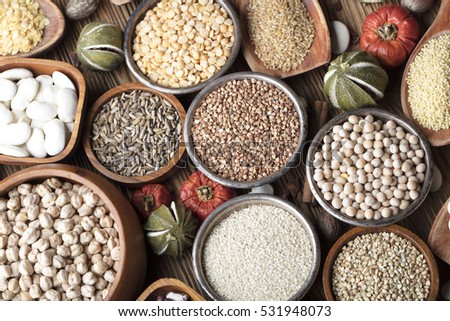 Healthy food and diet theme. Lentils, peas, beans, protein food in bowls, dry fruits and chili on a wooden table. Top view. Spices star anise and cinnamon
