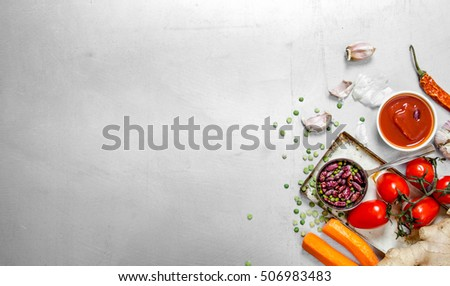 Healthy food . Raw vegetables with beans and spices. On the steel background