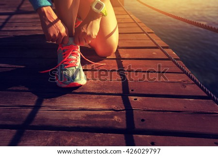 healthy lifestyle sports woman tying shoelace on wooden boardwalk sunrise seaside