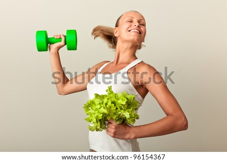 Healthy lifestyle - tanned woman lifting dumbbell and growing green salad