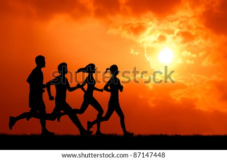 healthy man and woman group running at sunset silhouetted