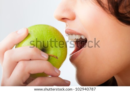 Healthy nutrition and healthy teeth or diet, young woman bites in a fresh apple