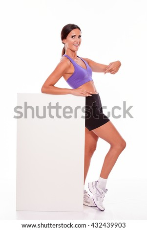 Healthy smiling brunette woman holding and pointing at blank placard with one hand while looking at camera and wearing violet and black gymnastic clothing, isolated