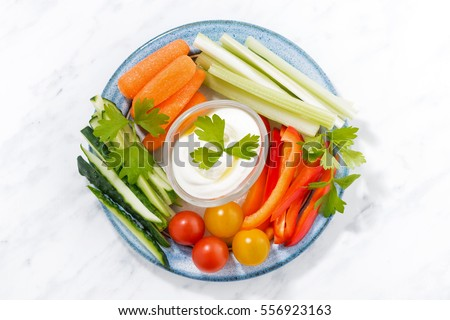 healthy snacks, mixed fresh vegetables and yogurt on a plate, top view, horizontal