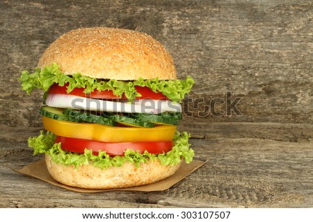 Healthy vegan burger with raw vegetables on old wooden background