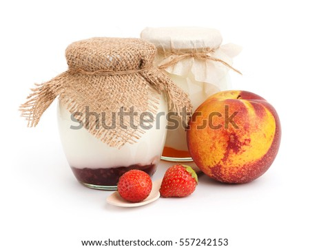 Healthy yogurts in glass jars with peach and strawberries