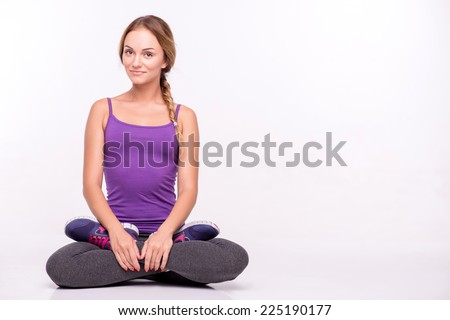 Healthy young sportswoman does the exercises sitting in lotus pose holding hands on knees isolated on white background with copy place