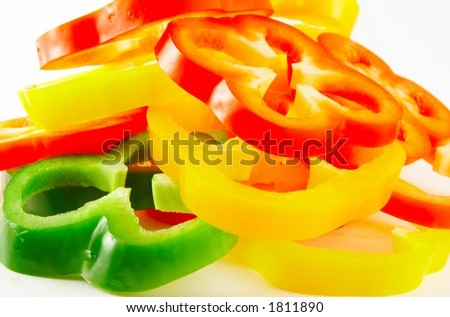Heap of colourful sliced bell peppers - white background
