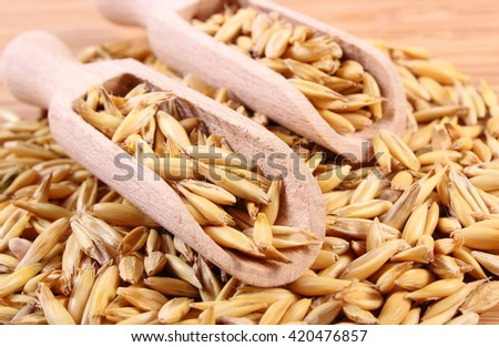 Heap of organic oat grains on wooden spoon lying on wooden table, healthy food and nutrition