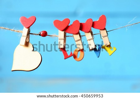 Heart and colored letters with the word love hanging from a rope on a blue background. Valentines day.