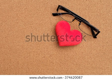 heart and glasses on wood