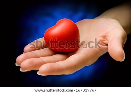Heart in hand on black and blue background