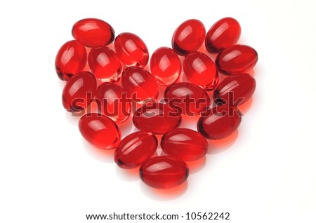 Heart made of red capsules on white background