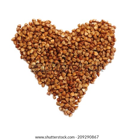 Heart shaped brown buckwheat, valentine heart of brown groats. Isolated on white background