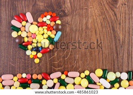 Heart shaped colorful medical pills, capsules or supplements for therapy, concept of treatment and health care, copy space for text or inscription