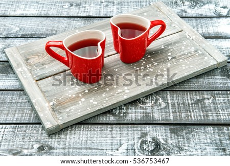 Heart shaped cups with red drink on rustic wooden background. Valentines day