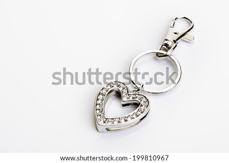 Heart shaped jewelery and key chain on red velvet