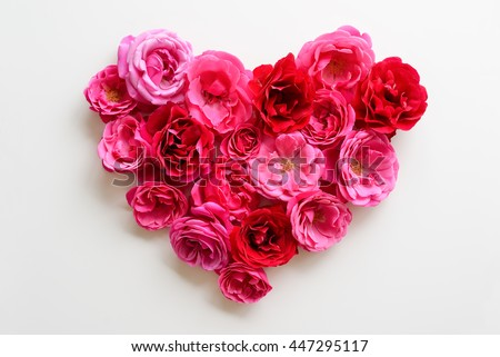 Heart symbol made of pink roses on white background. Flat lay beautiful flowers. Roses for love concept.