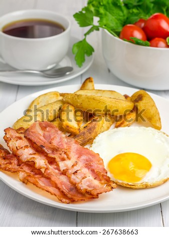 Hearty breakfast with bacon, fried egg, potato and cup of coffee