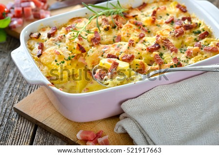 Hearty potato gratin with parmesan cheese, cream and delicious cured bacon from South Tyrol freshly served from the oven on a wooden table