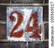 heavily weathered house number twenty four, hand painted on a metal plate - stock photo