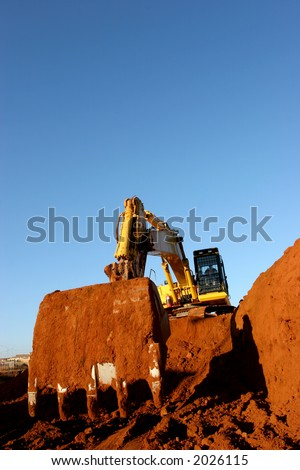 Heavy construction equipment digging into ground away
