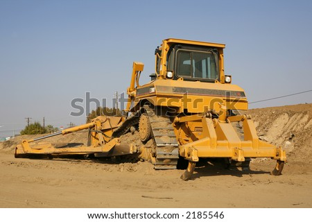 Heavy construction equipment with ripper on one end and blade and blade extension on the other