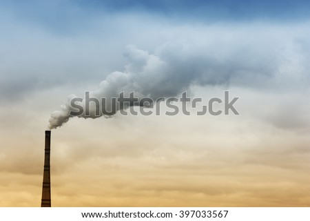 Heavy industrial smoke erupts from factory's chimney into the sky with blue and yelllow colors