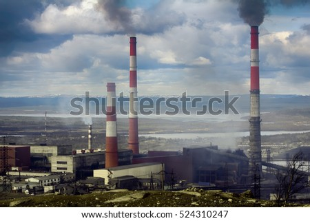 Heavy industry. Old forties Copper-Nickel plant in smoke on background of autumn forest and dead land. Air pollution