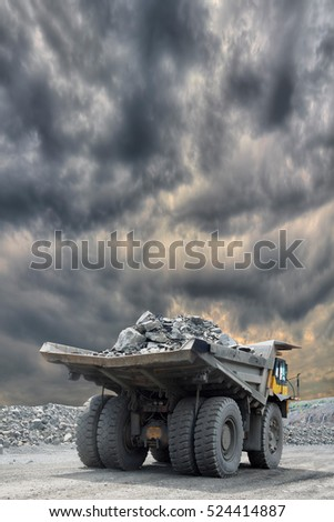 Heavy mining truck loaded with iron ore driving along the opencast with stormy clouds on the background