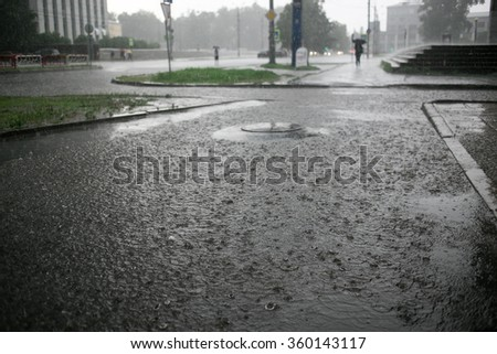 heavy rain drops falling on city street during downpour