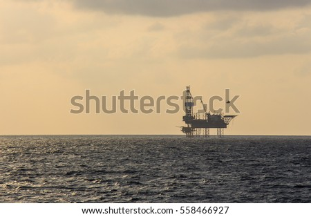 helicopter and gas rig silhouette in the Gulf of Thailand